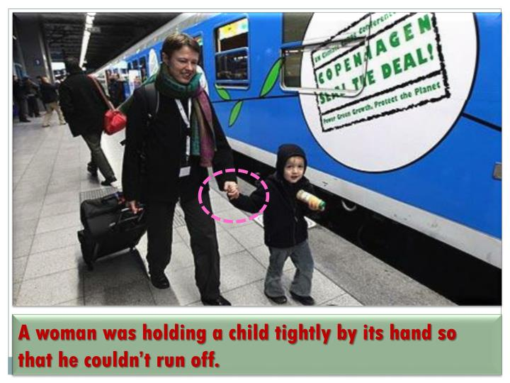 A woman was holding a child tightly by its hand so that he couldn't run off.