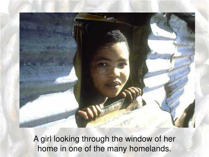 A girl looking through the window of her home in one of the many homelands.