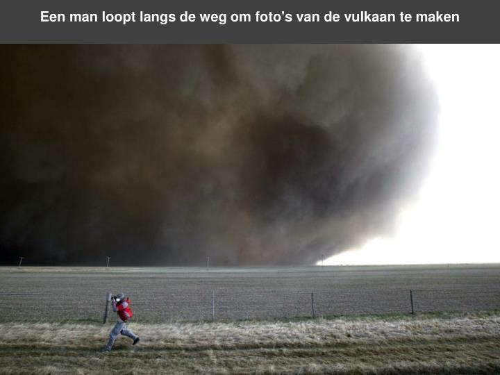 Een man loopt langs de weg om foto's van de vulkaan te maken