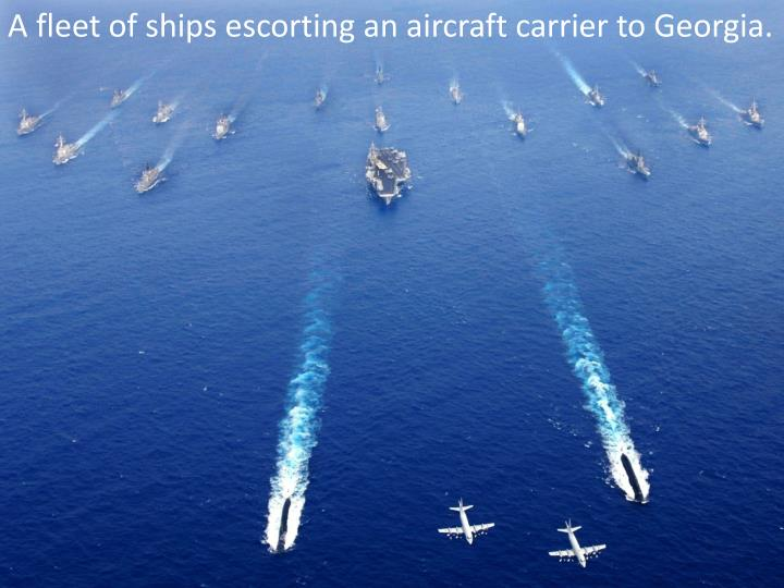 A fleet of ships escorting an aircraft carrier to Georgia.