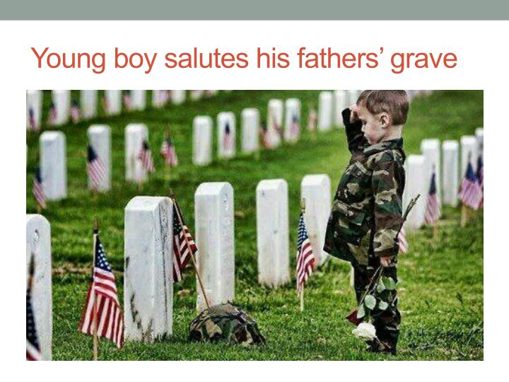 Young boy salutes his fathers' grave