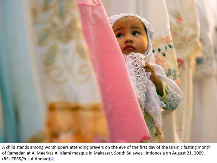 A child stands among worshippers attending prayers on the eve of the first day of the Islamic fasting month of Ramadan at Al