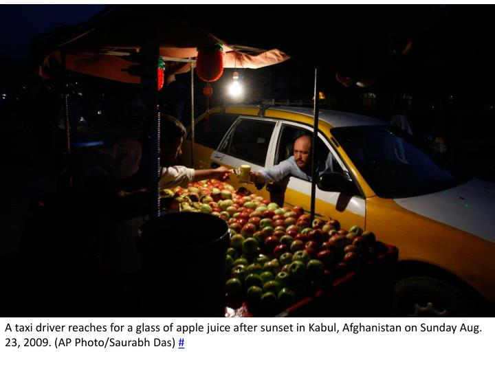 A taxi driver reaches for a glass of apple juice after sunset in Kabul, Afghanistan on Sunday Aug. 23, 2009. (AP Photo/