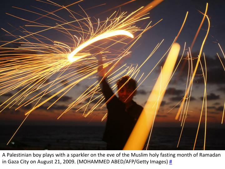 A Palestinian boy plays with a sparkler on the eve of the Muslim holy fasting month of Ramadan in Gaza City on August 21, 2009. (MOHAMMED ABED/AFP/Getty Images)