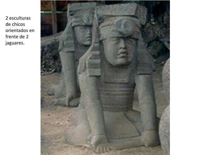 2 esculturas de chicos orientados en frente de 2 jaguares.