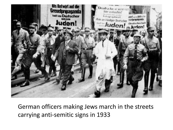 German officers making Jews march in the streets carrying anti-