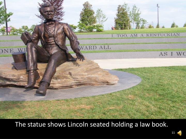 The statue shows Lincoln seated holding a law book.