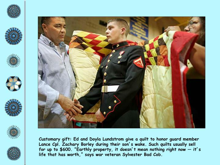 Customary gift: Ed and Doyla Lundstrom give a quilt to honor guard member Lance Cpl. Zachary Borley during their son