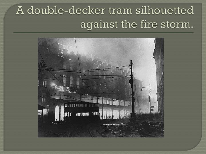 A double-decker tram silhouetted against the fire storm.