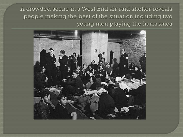 A crowded scene in a West End air raid shelter reveals people making the best of the situation including two young men playing the harmonica