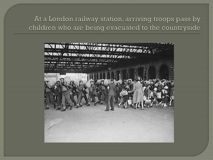 At a London railway station, arriving troops pass by children who are being evacuated to the country...