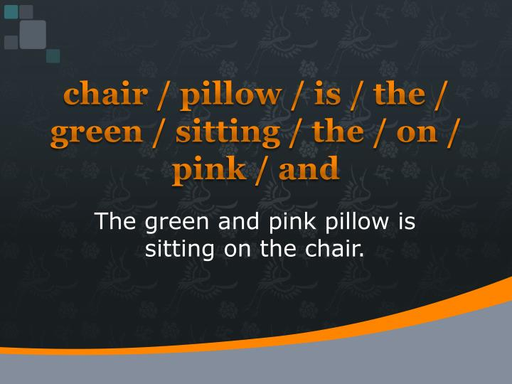 chair / pillow / is / the / green / sitting / the / on / pink / and