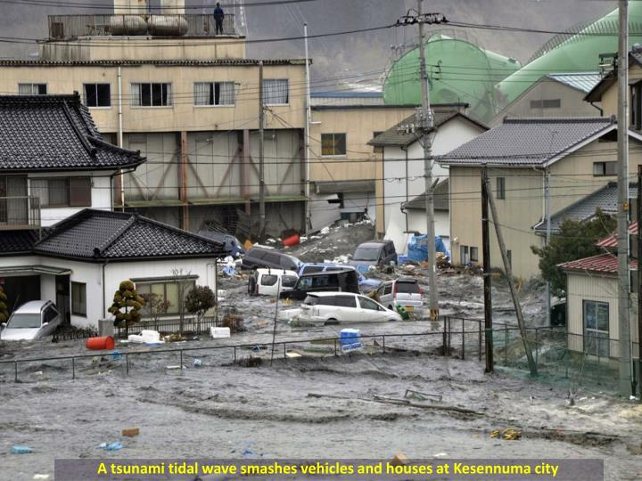 A tsunami tidal wave smashes vehicles and houses at