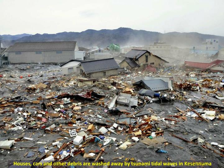 Houses, cars and other debris are washed away by tsunami tidal waves in