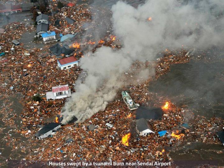 Houses swept by a tsunami burn near Sendai Airport
