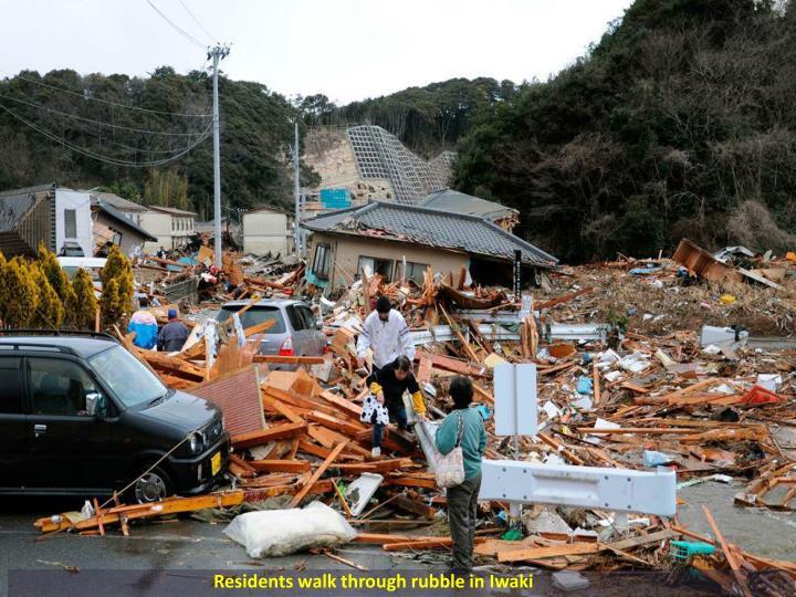 Residents walk through rubble in Iwaki