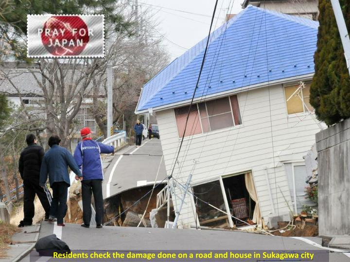 Residents check the damage done on a road and house in