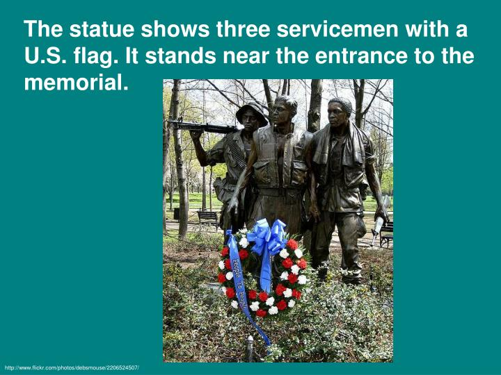 The statue shows three servicemen with a U.S. flag. It stands near the entrance to the memorial.