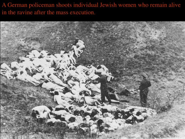 A German policeman shoots individual Jewish women who remain alive in the ravine after the mass execution.