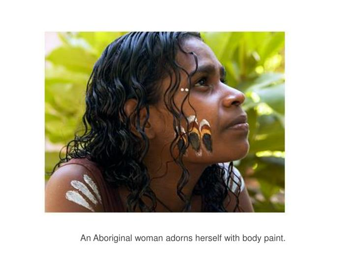 An Aboriginal woman adorns herself with body paint.
