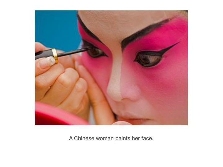 A Chinese woman paints her face.