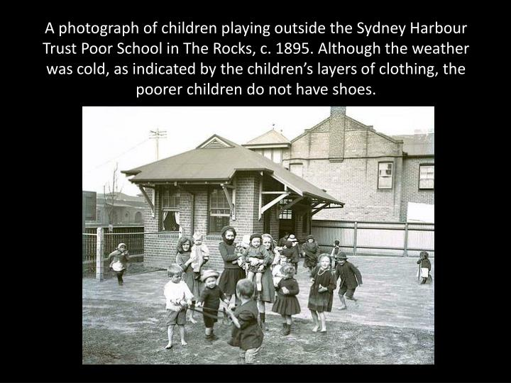A photograph of children playing outside the Sydney Harbour Trust Poor School in The Rocks, c. 1895. Although the weather was cold, as indicated by the children's layers of clothing, the poorer children do not have shoes.