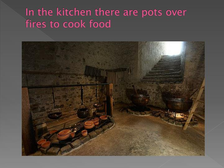 In the kitchen there are pots over fires to cook food
