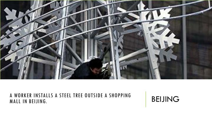 A worker installs a steel tree outside a shopping mall in Beijing.