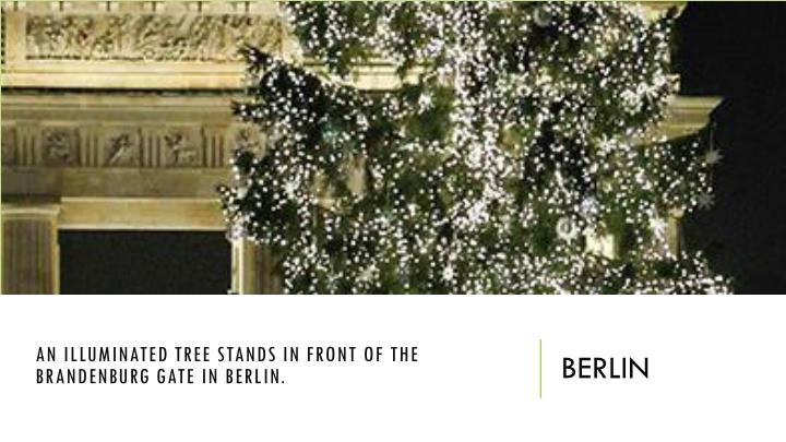 An illuminated tree stands in front of the Brandenburg Gate in Berlin.