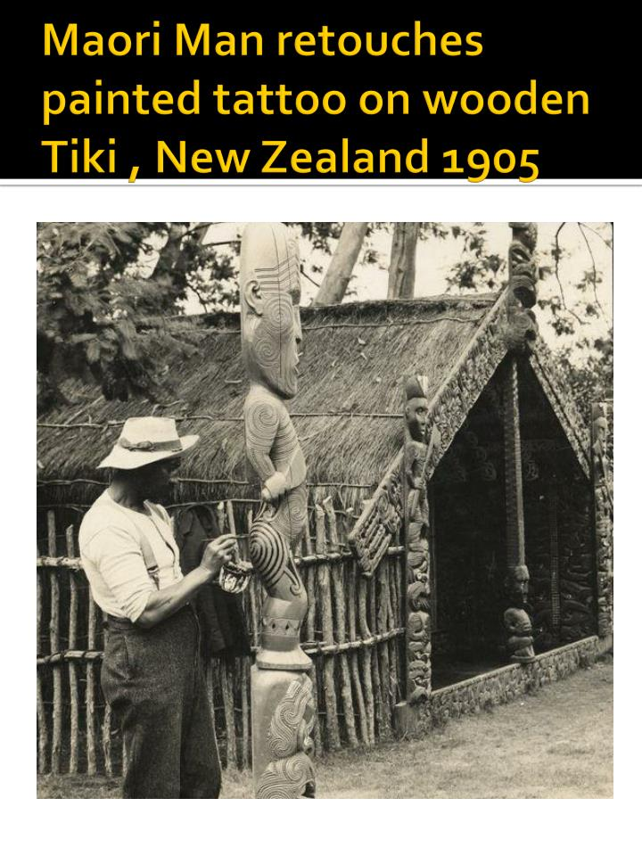 Maori Man retouches painted tattoo on wooden Tiki , New Zealand 1905