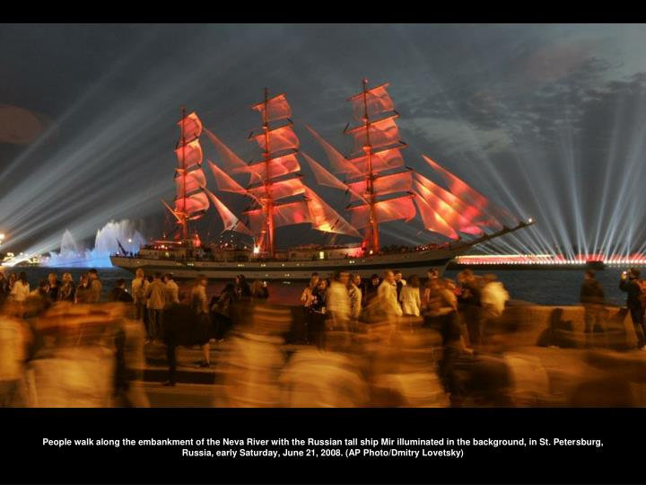 People walk along the embankment of the Neva River with the Russian tall ship Mir illuminated in the background, in St. Petersburg, Russia, early Saturday, June 21, 2008. (AP Photo/Dmitry Lovetsky)