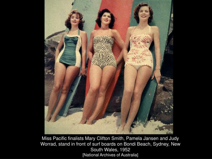 Miss Pacific finalists Mary Clifton Smith, Pamela Jansen and Judy Worrad, stand in front of surf boards on Bondi Beach, Sydney, New South Wales, 1952
