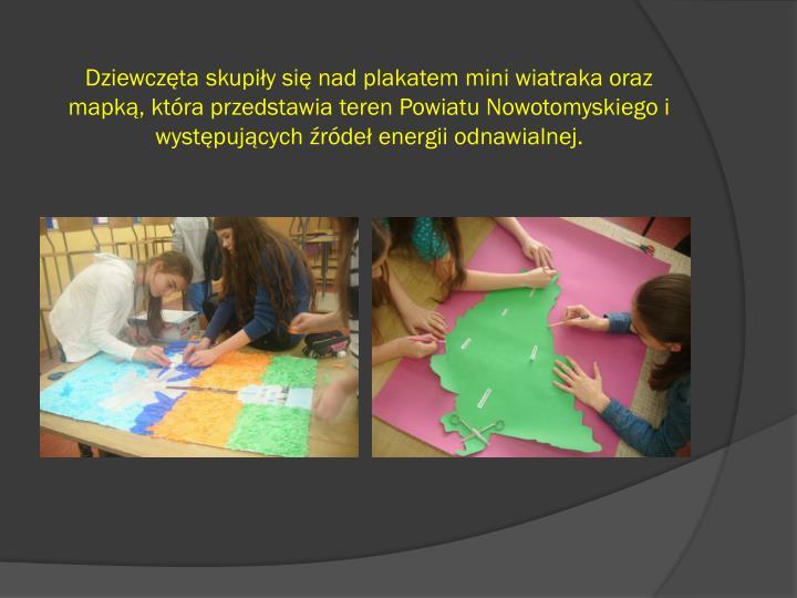 Dziewczta skupiy si nad plakatem mini wiatraka oraz mapk, ktra przedstawia teren Powiatu Nowotomyskiego i wystpujcych rde energii odnawialnej.