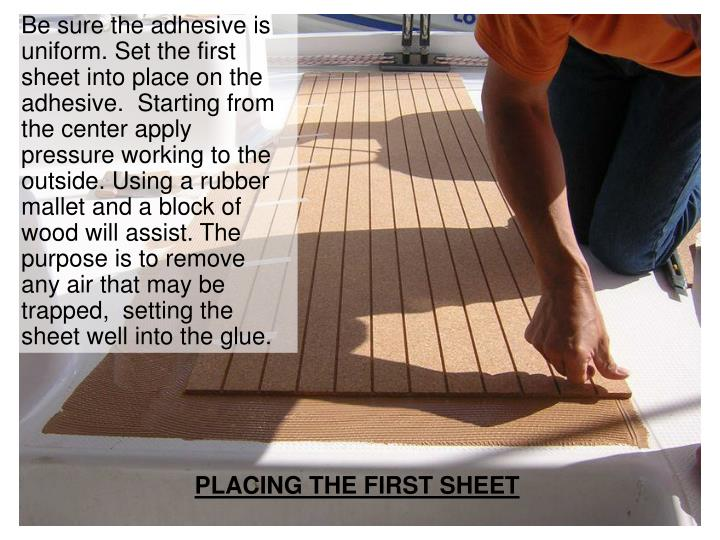 Be sure the adhesive is uniform. Set the first sheet into place on the adhesive.  Starting from the center apply pressure working to the outside. Using a rubber mallet and a block of wood will assist. The purpose is to remove any air that may be trapped,  setting the sheet well into the glue.
