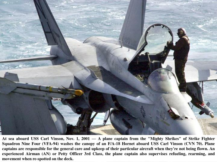 "At sea aboard USS Carl Vinson, Nov. 1, 2001 — A plane captain from the ""Mighty Shrikes"" of Strike Fighter Squadron Nine Four (VFA-94) washes the canopy of an F/A-18 Hornet aboard USS Carl Vinson (CVN 70). Plane captains are responsible for the general care and upkeep of their particular aircraft when they're not being flown. An experienced Airman (AN) or Petty Officer 3rd Class, the plane captain also supervises refueling, rearming, and movement when re-spotted on the deck."