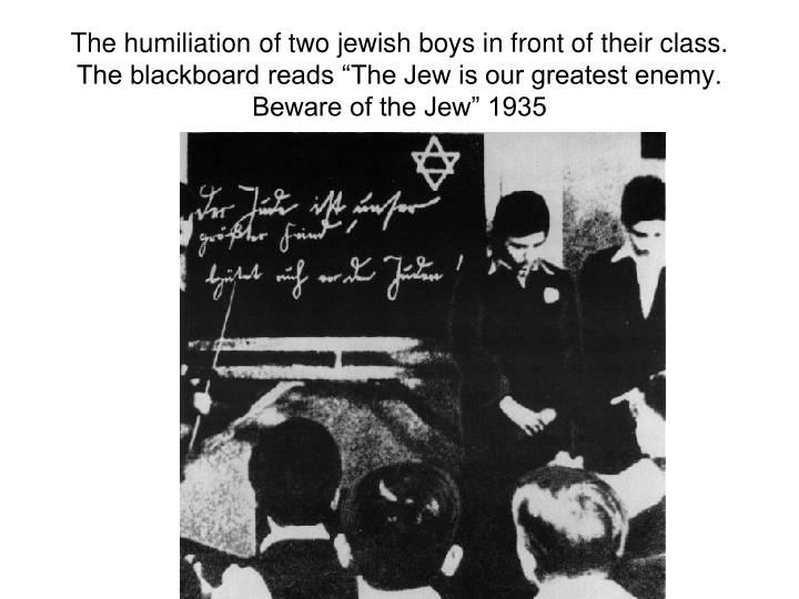 "The humiliation of two jewish boys in front of their class. The blackboard reads ""The Jew is our greatest enemy. Beware of the Jew"" 1935"