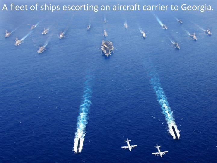 A fleet of ships escorting an aircraft carrier to Georgia.