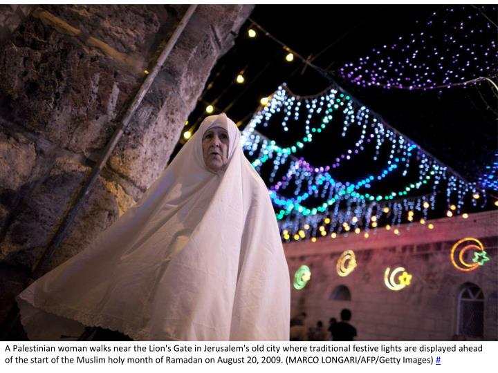 A Palestinian woman walks near the Lion's Gate in Jerusalem's old city where traditional festive lights are displayed ahead of the start of the Muslim holy month of Ramadan on August 20, 2009. (MARCO LONGARI/AFP/Getty Images)