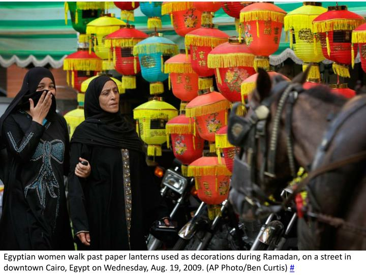 Egyptian women walk past paper lanterns used as decorations during Ramadan, on a street in downtown Cairo, Egypt on Wednesday, Aug. 19, 2009. (AP Photo/Ben Curtis)