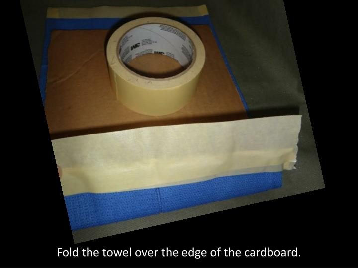 Fold the towel over the edge of the cardboard.