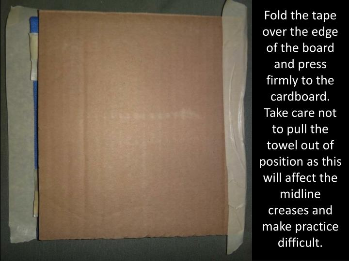 Fold the tape over the edge of the board and press firmly to the cardboard.  Take care not to pull the towel out of position as this will affect the midline creases and make practice difficult.