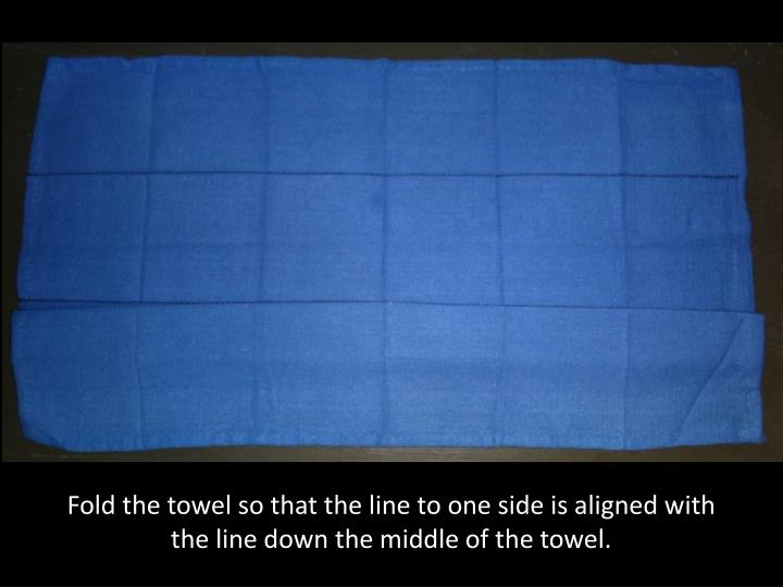Fold the towel so that the line to one side is aligned with the line down the middle of the towel.