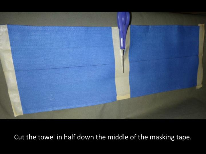 Cut the towel in half down the middle of the masking tape.