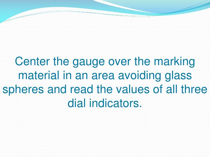 Center the gauge over the marking material in an area avoiding glass spheres and read the values of all three dial indicators.