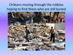 chileans moving through the rubbles hoping to find those who are still buried