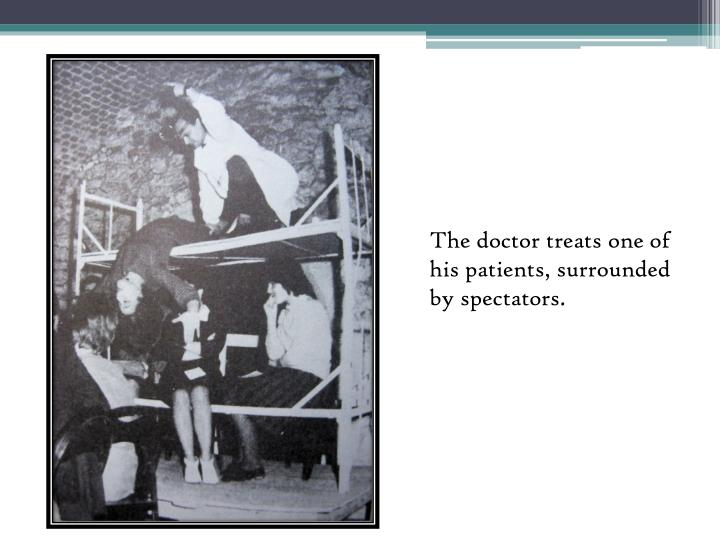 The doctor treats one of his patients, surrounded by spectators.