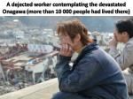 a dejected worker contemplating the devastated onagawa more than 10 000 people had lived there